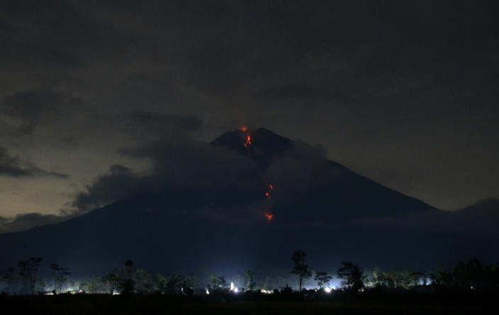 Hot lava flows from the crater of Mount Semeru as its activity continues in this photo taken with slow shutter speed in Lumajang, East Java, Indonesia, late Sunday, Jan. 17, 2021. The highest volcano on Indonesia's most densely populated island of Java, spewed hot clouds as far away as 4.5 kilometers (nearly 3 miles) on Saturday. There were no immediate evacuations, but the National Disaster Mitigation Agency warned people who live in the villages on the slopes of the 3,676-meter (12,060-foot)-high mountain to be vigilant in looking for signs of danger. (AP Photo/Hendra Permana)