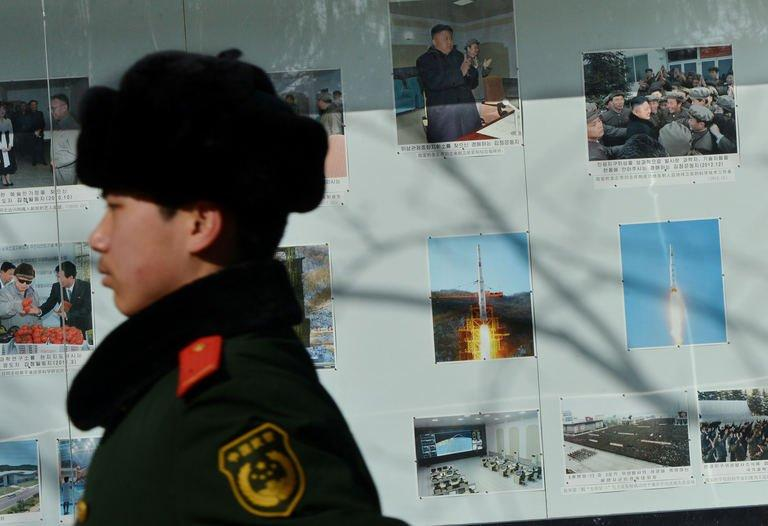 A Chinese policeman marches past photos of North Korea's recent rocket launch in Beijing on February 6, 2013