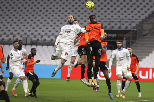 Marseille's Dario Benedetto, left, Marseille's Florian Thauvin, second left, jumps for the ball with Rennes' M'Baye Niang, right, during the French League One soccer match between Marseille and Reims at the Stade Velodrome in Marseille, southern France, Saturday Dec. 19, 2020. (AP Photo/Daniel Cole)
