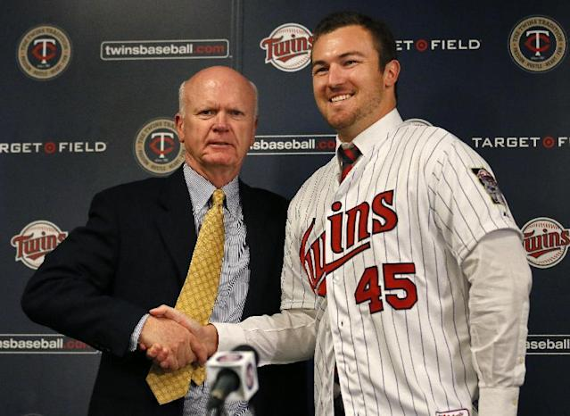 Minnesota Twins GM Terry Ryan, left, shakes hands with pitcher Phil Hughes Thursday Dec. 5, 2013 in Minneapolis. Twins finalized a $24 million, three-year contract with Hughes after he passed his physical Thursday. (AP Photo/The Star Tribune, Brian Peterson)