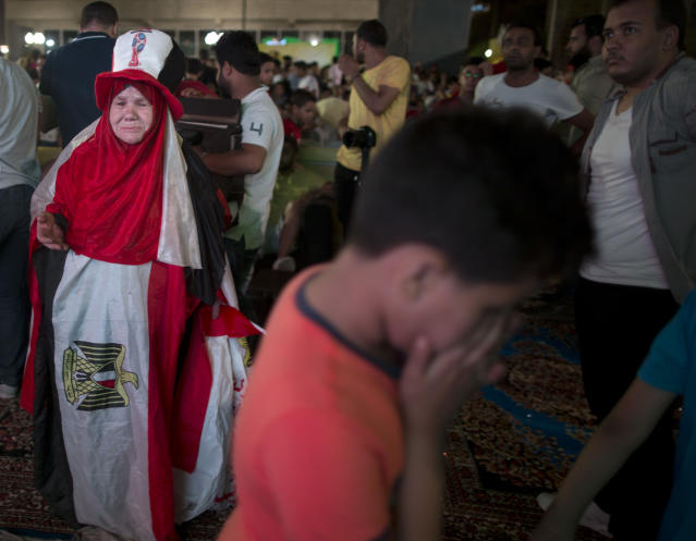 An Egyptian woman wearing the national flag cries as she leaves the display of the group A World Cup match between Egypt and Russia on a giant screen at Al Jazera youth club, in Cairo, Egypt, Tuesday, June 19, 2018. Russia scored three goals in a 15-minute span early in the second half to set up a 3-1 win over Egypt on Tuesday, moving the host nation to the brink of the World Cup's knockout stage. (AP Photo/Amr Nabil)