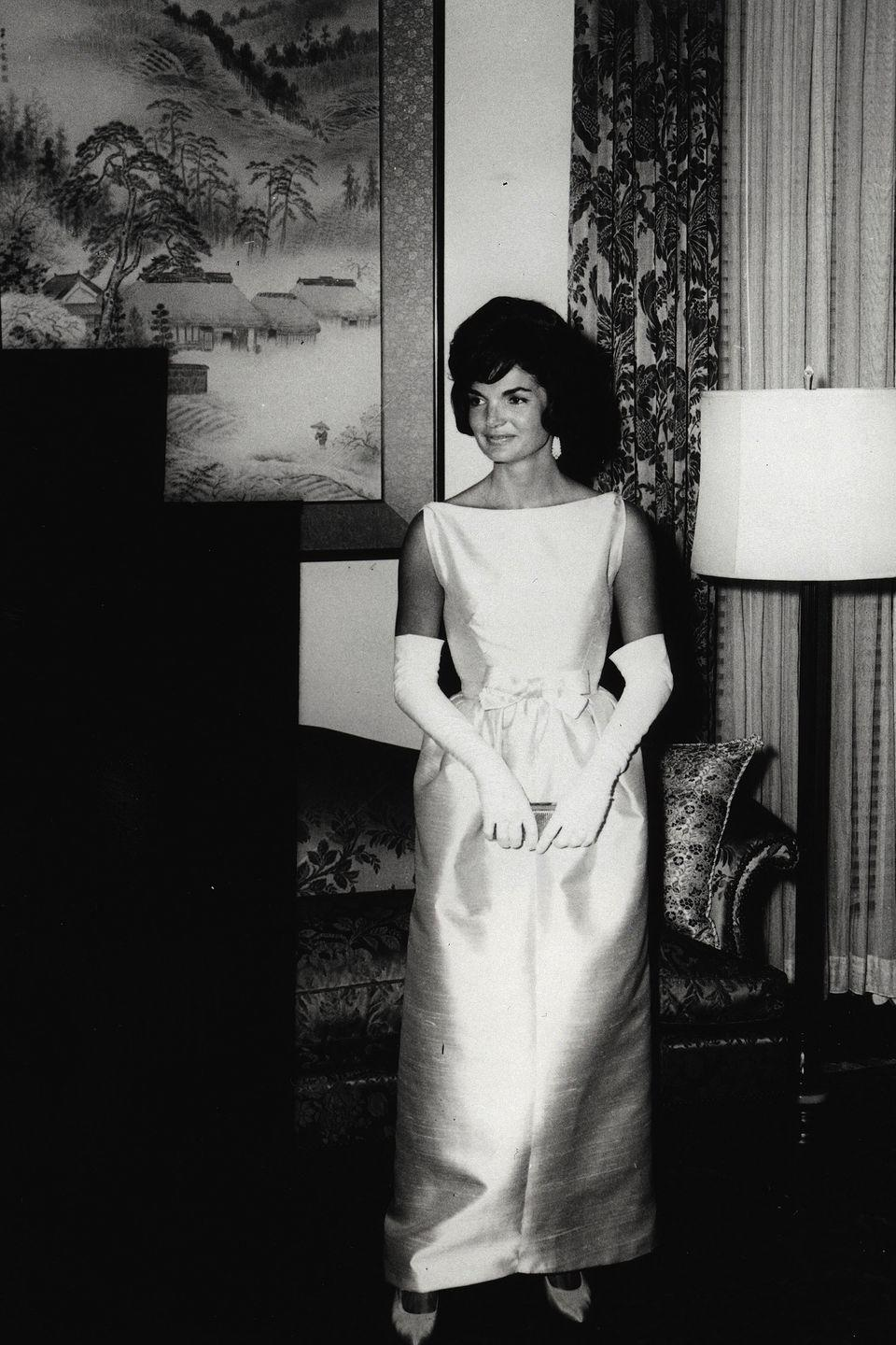 <p>Kennedy again donned gloves and a boatneck gown to attend a dinner at the Japanese Embassy in 1961. That simple bow ties up the luxe white look.</p>