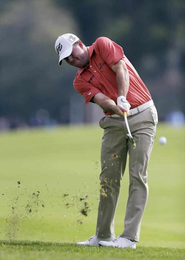 Robert Garrigus hits his approach shot from the rough on the second hole in the third round of the Northern Trust Open golf tournament at Riviera Country Club in the Pacific Palisades area of Los Angeles Saturday, Feb. 15, 2014. (AP Photo/Reed Saxon)