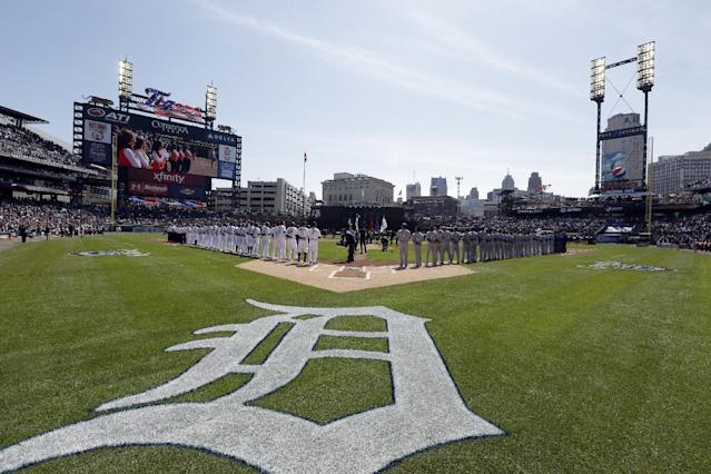 The Kansas City Royals and the Detroit Tigers stand for the national anthem before a baseball game in Detroit, Monday, March 31, 2014. (AP Photo/Carlos Osorio)