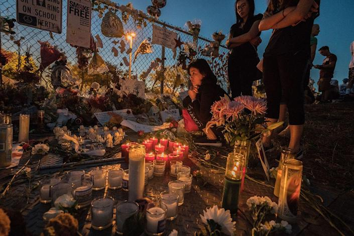 <p>A student at Stoneman Douglas High School in Parkland, Florida mourns at the memorials outside of the school less than two weeks after a former student shot and killed three teachers and 14 kids. </p>