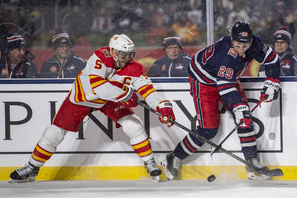 Calgary Flames' Mark Giordano (5) and Winnipeg Jets' Patrik Laine (29) battle for the puck during the first period of an NHL Heritage Classic in Regina, Canada, Saturday, Oct. 26, 2019. (Liam Richards/The Canadian Press via AP)