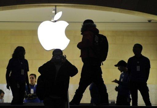 People walk past the Apple logo at the Apple Store at Grand Central Terminal in New York on January 25, 2013. Apple shares extended their losses, ending a miserable week for the California tech giant as it surrendered its position as the world's biggest company based on market value.