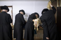 Ultra-Orthodox Jews swing chickens over their heads during the Kaparot ritual, in Bnei Brak, Israel, Sunday, Sept 27, 2020. Observant Jews believe the ritual transfers one's sins from the past year into the chicken, and is performed before the Day of Atonement, Yom Kippur, the holiest day in the Jewish year which starts at sundown Sunday. The solemn Jewish holiday of Yom Kippur, which annually sees Israeli life grind to a halt, arrived on Sunday in a nation already under a sweeping coronavirus lockdown. (AP Photo/Oded Balilty)