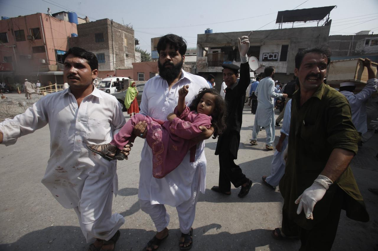 A volunteer carries a girl, who was injured in a bomb blast as she arrives at a hospital in Peshawar September 29, 2013. Twin blasts in the northwestern Pakistan city of Peshawar killed 33 people and wounded 70 on Sunday, a week after two bombings at a church in the frontier city killed scores, police and hospital authorities said.REUTERS/ Fayaz Aziz (PAKISTAN - Tags: POLITICS CIVIL UNREST CRIME LAW)