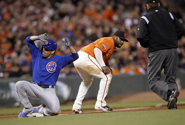 Chicago Cubs' David DeJesus, left, slides into third base past San Francisco Giants third baseman Pablo Sandoval for a triple during the fifth inning of a baseball game on Friday, July 26, 2013, in San Francisco. (AP Photo/Tony Avelar)