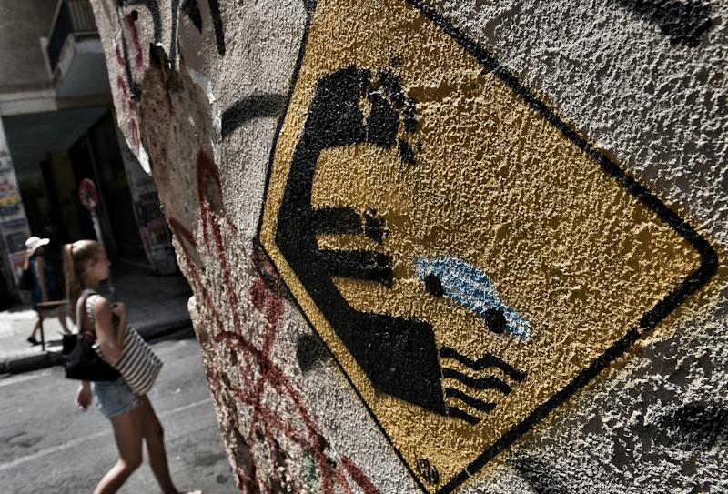 A woman walks past a wall bearing graffiti concerning Greece's possible exit from the euro in Athens on June 28, 2015