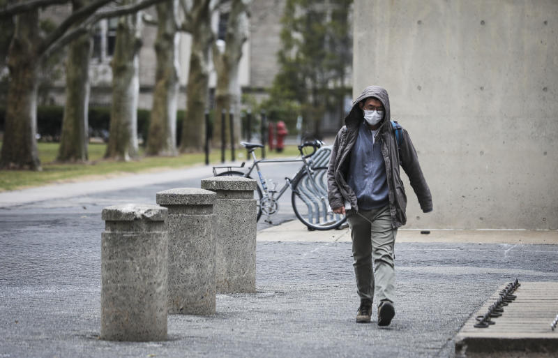 CAMBRIDGE, MA - MARCH 10: CAMBRIDGE, MA - MARCH 10: A person wears a mask while walking though MIT's campus in Cambridge, MA on March 10, 2020. Some colleges have moved all classes online amid coronavirus concerns, but MIT has only moved its large classes and lectures offsite. (Photo by Erin Clark for The Boston Globe via Getty Images)