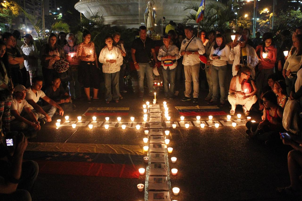 Anti-government protesters place candles next to photographs of victims of violence during a prayer ceremony in Caracas March 18, 2014. A Venezuela National Guard captain died on Monday after being shot in the head during a demonstration, the military said, the 29th fatality in six weeks of clashes between protesters and security forces. REUTERS/Christian Veron (VENEZUELA - Tags: POLITICS CIVIL UNREST)