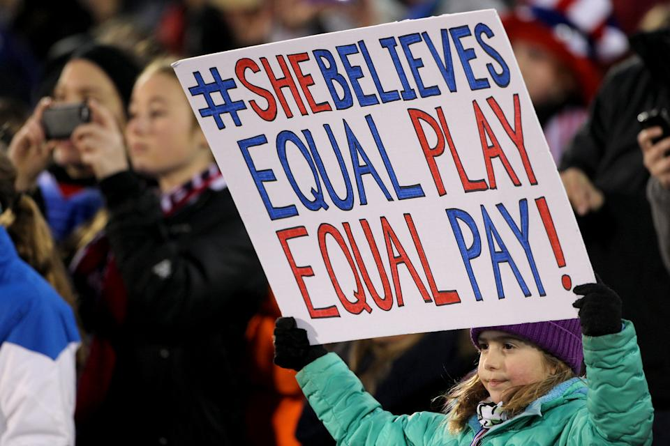 """A young fan holds an """"equal pay"""" banner during a USWNT friendly against Colombia in 2016. (Photo Tim Clayton/Corbis via Getty Images)"""