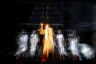 """In this photograph shot with a slow shutter speed Romanian Jewish actress Maia Morgernstern, center, performs alongside fellow actresses of the Jewish State Theatre, wearing face masks for protection against COVID-19 infection, during rehearsals for the premiere of the """"The Beautiful Days of My Youth"""" play, based on the diary of Romanian Jewish Holocaust survivor Ana Novac, in Bucharest, Thursday, Oct. 15, 2020. The latest première at the Jewish State Theater in the Romanian capital, Bucharest, explores the horrors of the Holocaust via a survivor's memories of the Auschwitz and Plaszow concentration camps. (AP Photo/Andreea Alexandru)"""