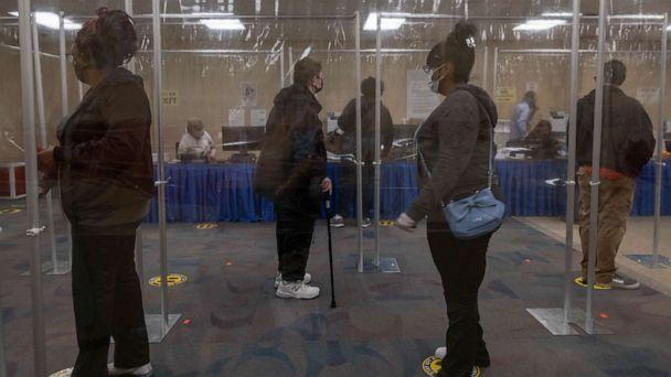 PHOTO: Ohio residents wait in line behind plastic barriers and stand six feet apart to help protect people from Coronavirus during early voting in Toledo, Oct. 6, 2020. (Seth Herald/AFP via Getty Images)