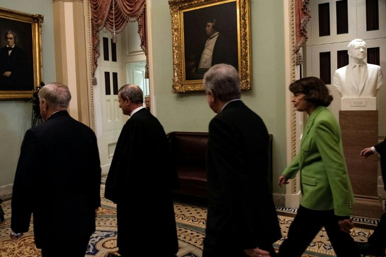 (From L) US Supreme Court Chief Justice John Roberts, Republican Senator Lindsey Graham, Republican Senator Roy Blunt and Democratic Senator Dianne Feinstein leave after the Senate voted to acquit President Donald Trump