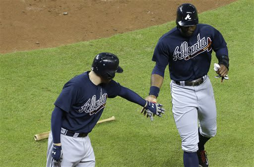 Atlanta Braves' Jason Heyward, right, is met by Freddie Freeman, left, after scoring on a double by Justin Upton in the third inning during a baseball game against the Miami Marlins,Tuesday, July 9, 2013 in Miami. (AP Photo/Lynne Sladky)