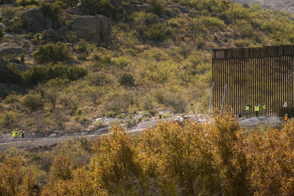 With Mexico to the top, border wall construction continues along a cleared pathway, Wednesday, Dec. 9, 2020, in Guadalupe Canyon, Ariz. Construction of the border wall, mostly in government owned wildlife refuges and Indigenous territory, has led to environmental damage and the scarring of unique desert and mountain landscapes that conservationists fear could be irreversible. (AP Photo/Matt York)