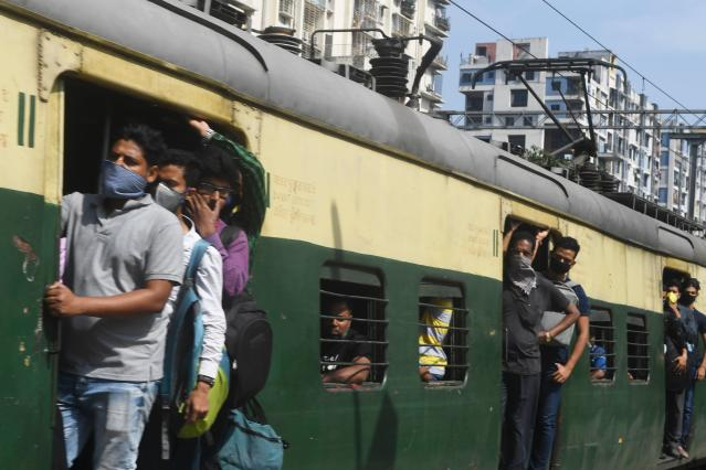 Passengers wearing facemasks amid concerns over the spread of the COVID-19 novel coronavirus, travel in a train at the Bidhan Nagar Road railway station, in Kolkata on March 21, 2020. (Photo by Dibyangshu SARKAR / AFP) (Photo by DIBYANGSHU SARKAR/AFP via Getty Images)