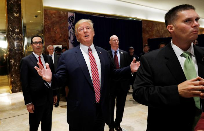 """At New York's Trump Tower, President Trump stops to respond to more questions about his responses to the violence, injuries and deaths at the """"Unite the Right"""" rally in Charlottesville. He is flanked by Treasury Secretary Steven Mnuchin, left, and U.S. Secret Service agents, right, after speaking to the media, Aug. 15, 2017. (Photo: Kevin Lamarque/Reuters)"""