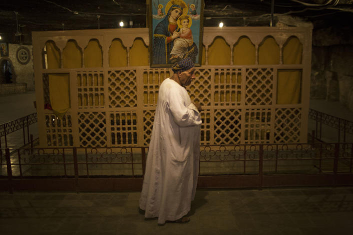 An Egyptian Coptic walks beside the altarpiece within a cave at Al-Mahraq monastery in Assiut, Upper Egypt, Tuesday, Aug. 6, 2013. Islamists may be on the defensive in Cairo, but in Egypt's deep south they still have much sway and audacity: over the past week, they have stepped up a hate campaign against the area's Christians. Blaming the broader Coptic community for the July 3, 2013 coup that removed Islamist President Mohammed Morsi, Islamists have marked Christian homes, stores and churches with crosses and threatening graffiti. (AP Photo/Manu Brabo)