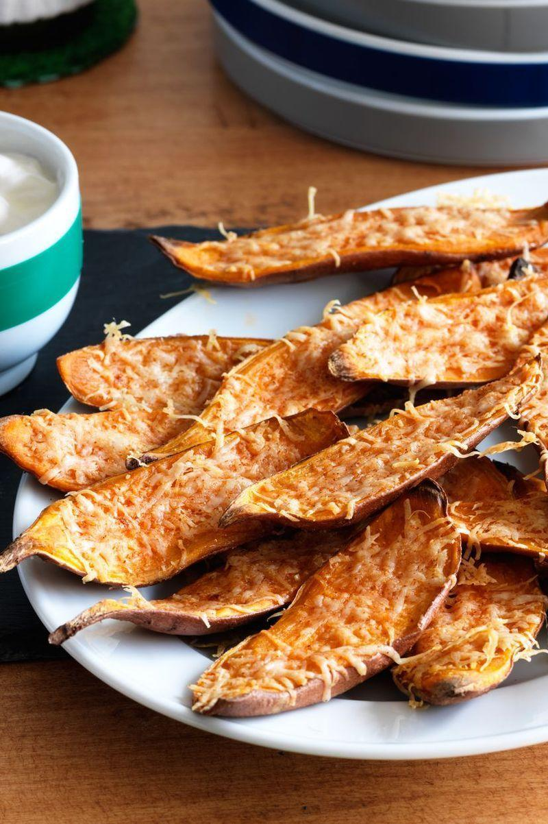 """<p>Give guests a spiced-up twist on the sweet potato side dishes with these cayenne pepper and cheese-sprinkled skins.</p><p><a href=""""https://www.womansday.com/food-recipes/food-drinks/recipes/a11250/sweet-potato-skins-recipe-122833/"""" rel=""""nofollow noopener"""" target=""""_blank"""" data-ylk=""""slk:Get the Sweet Potato Skins recipe."""" class=""""link rapid-noclick-resp""""><em><strong>Get the Sweet Potato Skins recipe. </strong></em></a></p>"""