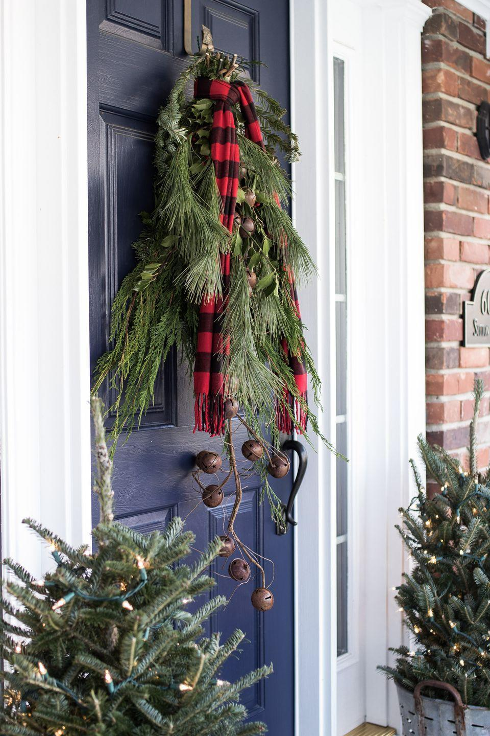 "<p>This brilliantly simple door decor from <a href=""http://www.onsuttonplace.com/2015/12/festive-frugal-christmas-porch-decor/"" rel=""nofollow noopener"" target=""_blank"" data-ylk=""slk:On Sutton Place"" class=""link rapid-noclick-resp"">On Sutton Place</a> features fresh pine bunches in lieu of a wreath, accented with a plaid scarf and a string of bells. </p>"