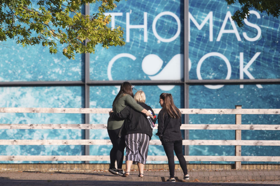People gather outside the headquarters of tour operator Thomas Cook, in Peterborough, England, which has ceased trading with immediate effect after failing in a final bid to secure a rescue package from creditors Monday Sept. 23, 2019. British tour company Thomas Cook collapsed early Monday after failing to secure emergency funding, leaving tens of thousands of vacationers stranded abroad. The British government said the return of the 178-year-old firm's 150,000 British customers now in vacation spots across the globe would be the largest repatriation in its peacetime history. (Joe Giddens/PA via AP)