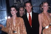 """<p>Halston's career boomed after launching his first perfume in 1975. He's photographed here with his """"Halstonettes"""" at a fragrance launch at Saks 5th Ave.</p>"""