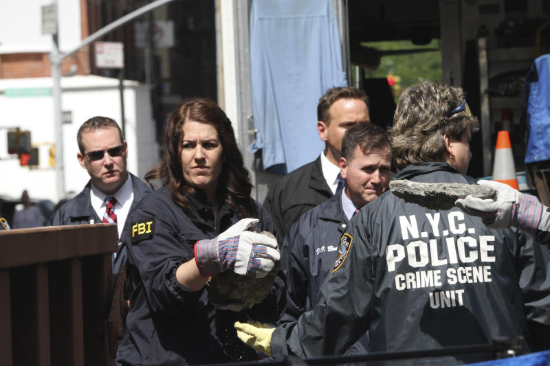Members of the FBI and NYPD carry pieces of concrete out of a basement of a building on the corner of Wooster Street and Prince Street in Manhattan during a renewed investigation into the 1979 disappearance of 6-year-old EtanPatz, on Friday, April 20, 2012 in New York. Patz vanished after leaving his family's home for a short walk to his school bus stop. NYPD spokesman Paul Browne says the building being searched for his remains is about a block from where the family lived. (AP Photo/Mary Altaffer)