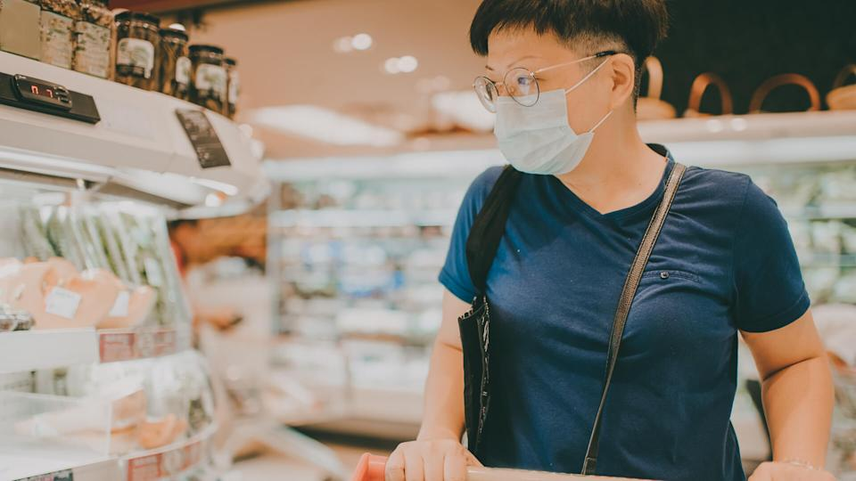 an asian chinese female wearing a mask going out shopping in supermarket.