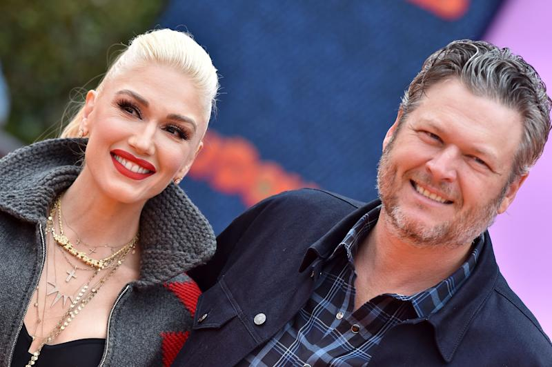 Blake Shelton looking amazing in a blue jacket with stripes T-shirt with Gwen Stefani rocking a grey sweater and pant to match