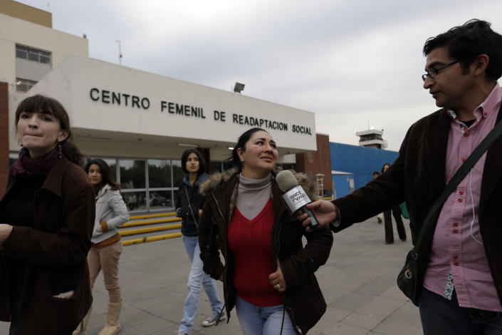"""Michelle Valadez, center, whose husband Ignacio was kidnapped, held for three months and killed in 2005, allegedly by the gang led by the Mexican then boyfriend of Frenchwoman Florence Cassez, cries while being interviewed by reporters outside a prison where Cassez had been held in Mexico City, Wednesday, Jan. 23, 2013. A Mexican Supreme Court panel voted Wednesday to release Cassez, a Frenchwoman who says she was unjustly sentenced to 60 years in prison for kidnapping and whose case became a cause celebre in France, straining relations between the two countries. A police convoy with sirens flashing escorted a white sports utility vehicle out of the prison where Cassez had been held later Wednesday, presumably carrying her to the Mexico City airport. Relatives of kidnap victims angrily shouted """"Killer!"""" as the vehicle pulled away. (AP Photo/Andres Leighton)"""