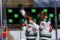 Minnesota Wild's Matt Dumba (24) raises his fist during the national anthems as Jonas Brodin (25) puts his hand on his shoulder before the team's hockey playoff game against the Vancouver Canucks in Edmonton, Alberta, Tuesday, Aug. 4, 2020. (Codie McLachlan/The Canadian Press via AP)