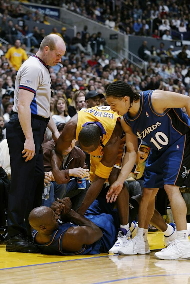 LOS ANGELES - MARCH 28: Michael Jordan #23 of the Washington Wizards is helped up from the floor by teammate Tyronn Lue #10 and Kobe Bryant #8 of the Los Angeles Lakers during the game at Staples Center on March 28, 2003 in Los Angeles, California. The Lakers won 108-94. NOTE TO USER: User expressly acknowledges and agrees that, by downloading and/or using this Photograph, User is consenting to the terms and conditions of the Getty Images License Agreement. (Photo by Robert Laberge/Getty Images)