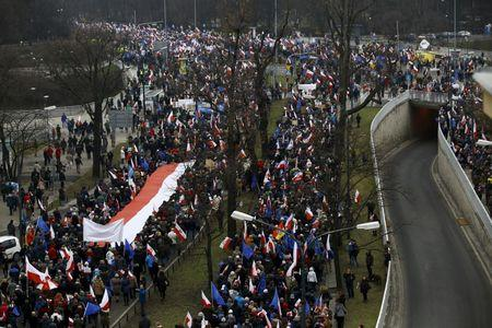 People hold a giant Polish national flag as they take part in a march demanding their government to respect the country's constitution in Warsaw