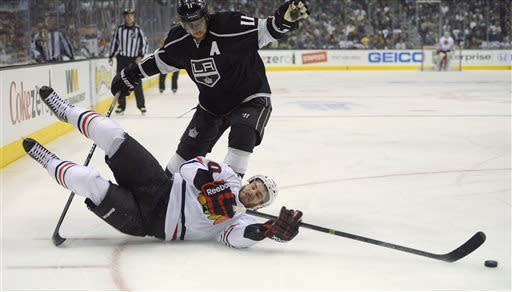 Chicago Blackhawks' Brandon Saad loses his footing as he brings the puck up the ice against Los Angeles Kings center Anze Kopitar (11) during the first period in Game 3 of the NHL hockey Stanley Cup playoffs Western Conference finals, Tuesday, June 4, 2013, in Los Angeles. (AP Photo/Mark J. Terrill)