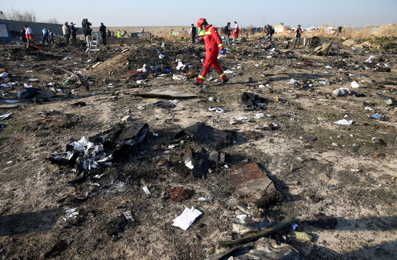 FILE PHOTO: A member of a rescue team walks among debris from a plane belonging to Ukraine International Airlines, that crashed after a take-off from Iran's Imam Khomeini airport, on the outskirts of Tehran