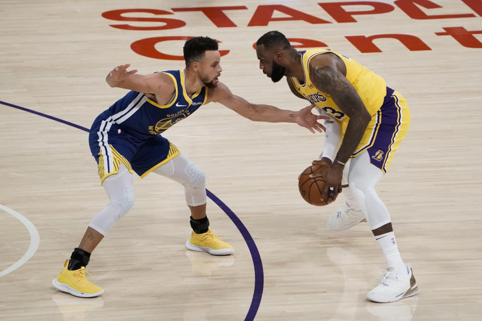 Golden State Warriors' Stephen Curry, left, pressures Los Angeles Lakers' LeBron James.