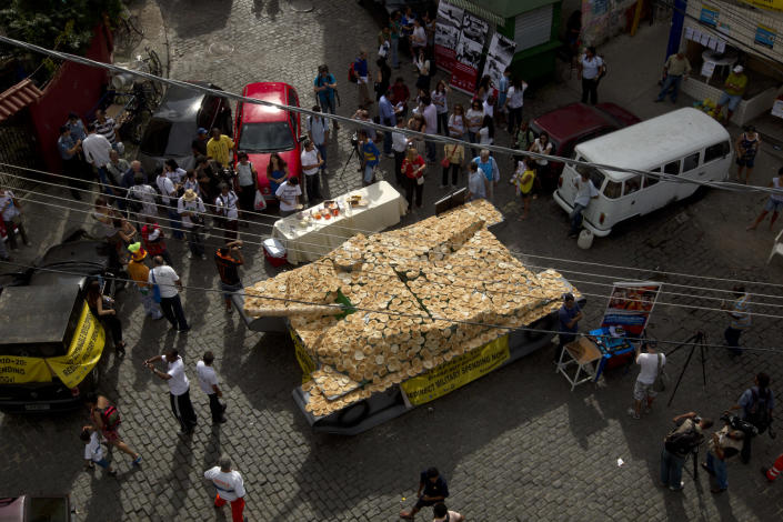 """A fake life-sized war tank covered by bread sits on display in the Santa Marta slum as part of a """"Bread not Bombs"""" protest on the sidelines of the Rio+20 UN Conference on Sustainable Development in Rio de Janeiro, Brazil, Tuesday, June 19, 2012. Activists placed the fake war tank covered with bread for residents to eat to protest military spending and demand that military spending be redirected for basic needs. (AP Photo/Silvia Izquierdo)"""