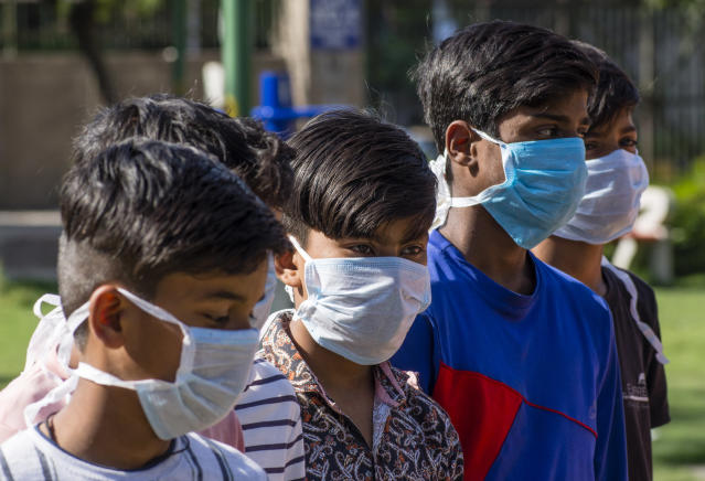 NEW DELHI, INDIA - MARCH 09: Indian children wearing masks amid the COVID-19 coronavirus fear on March 09, 2020 in New Delhi, India. Holi, the 2-day festival of colours will be celebrated across India on March 10. Hindus around the world celebrate Holi to mark the end of the winter and the beginning of the spring. This year amid the rise of coronavirus, the government has called for subdued celebration, with Prime Minister Narendra Modi cancelling a Holi event, the mood on the streets of India seems to hardy have dampened 47 people in India have so far tested positive for the deadly virus. (Photo by Yawar Nazir/ Getty Images)