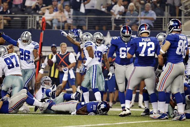 The Dallas Cowboys celebrate a fumble by New York Giants running back David Wilson (22) during the first half of an NFL football game, Sunday, Sept. 8, 2013, in Arlington, Texas. (AP Photo/LM Otero)
