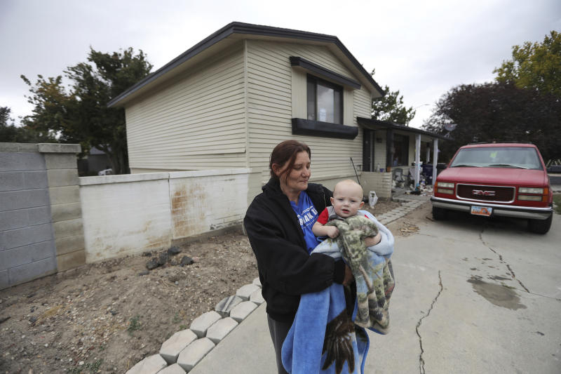 FILE - In this Oct. 9, 2019, file photo, Alanna Mabey holds her grandson in front of her home in West Valley City, Utah. Assessor Paul Petersen sold the house this spring as complaints mounted from neighbors in the working-class area in suburban Salt Lake City, said new owner Mabey. Authorities say Petersen used homes like this one to lodge pregnant women from the Marshall Islands who were offered money to come to the U.S. to give up their children for adoption. Petersen, the assessor of Arizona's most populous county, was charged in Utah, Arizona and Arkansas with counts including human smuggling, sale of a child, fraud, forgery and conspiracy to commit money laundering. The Maricopa County Board of Supervisors voted unanimously Wednesday, Oct. 23, to notify Petersen that it plans to consider suspending him for up to 120 days. It can't remove him from office and he's refused to resign. (AP Photo/Rick Bowmer, File)