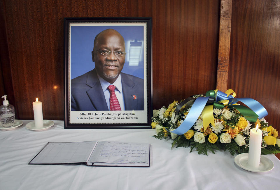 A portrait of Tanzania's former President John Magufuli is placed next to a book of condolences inside Tanzania's High Commission in Nairobi, Kenya Thursday, March 18, 2021. President John Magufuli of Tanzania, a prominent COVID-19 skeptic whose populist rule often cast his country in a harsh international spotlight, died aged 61 of heart failure, it was announced by Vice President Samia Suluhu Hassan on Wednesday. (AP Photo)