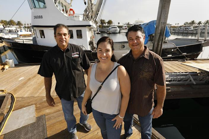A woman and two men pose for a photo on a pier.