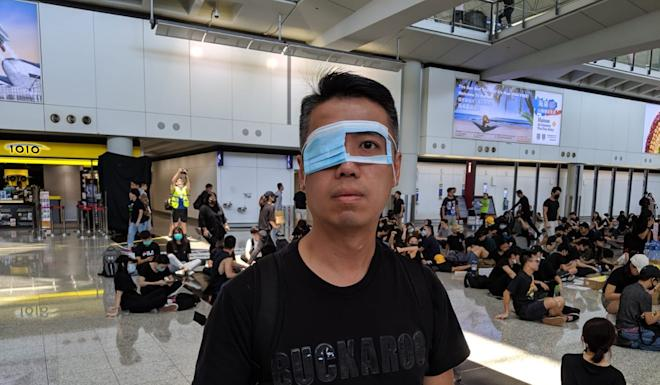 A protester at Hong Kong airport on Monday wears an eye mask in reference to the woman who suffered a serious eye injury after reportedly being hit by a beanbag round on Sunday. Photo: Sum Lok-kei