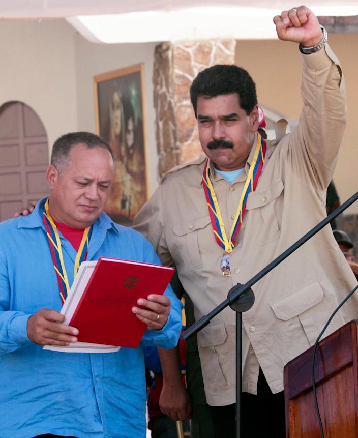 In this photo released by Miraflores Press Office, Venezuela's Nicolas Maduro, right, raises his arm as he stands with National Assembly President Diosdado Cabello during an event with soldiers at a military base in Coro, Venezuela, Monday, Sept. 30, 2013. Maduro said Monday that his government was expelling the top U.S. diplomat in Venezuela and two other embassy employees for allegedly conspiring with the political opposition. (AP Photo/Miraflores Press Office)