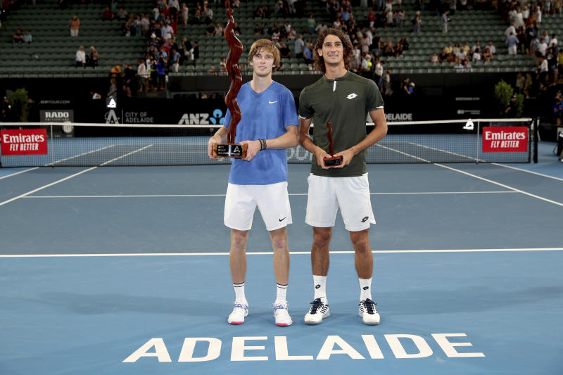 Russia's Andrey Rublev, left, and South Africa's Lloyd Harris pose during an award ceremony after their Adelaide International tennis final match in Adelaide, Saturday, Jan. 18, 2020. (AP Photo/James Elsby)