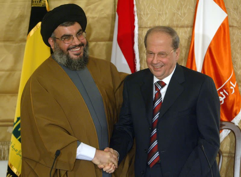 FILE PHOTO: Lebanon's Hezbollah leader Sheikh Hassan Nasrallah shakes hands with Christian leader Michel Aoun during news conference in Beirut